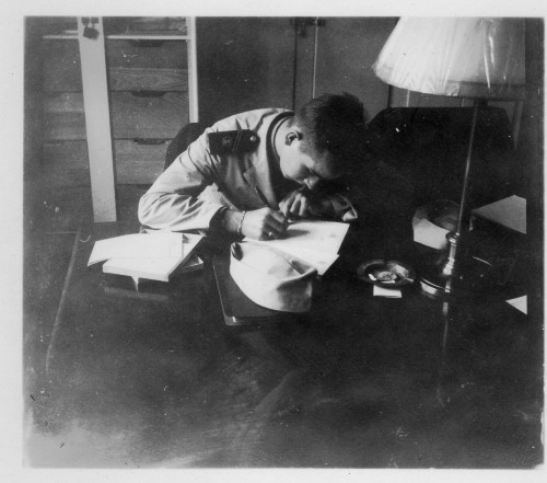 Vintage military soldier writing letter at desk.