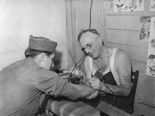 Vintage soldier military man getting tattoo on forearm.