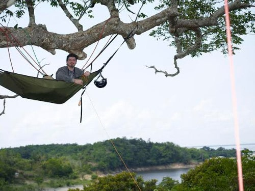 man in tree hammock hanging from large tree branch