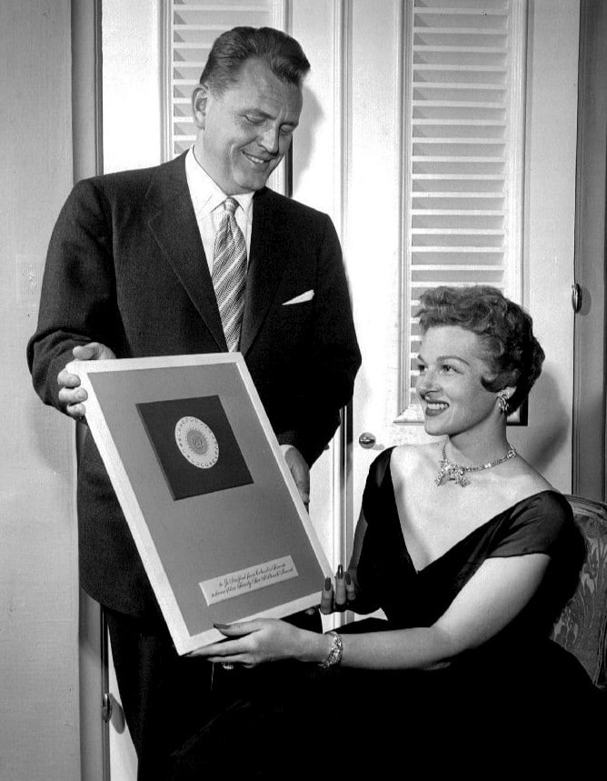 Vintage woman receiving award plaque smiling.