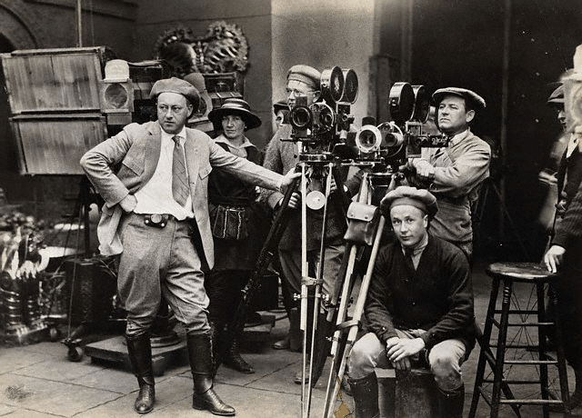 Vintage early 1900s film director with huge cameras on set.