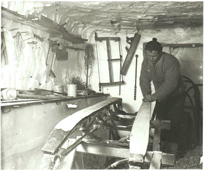 vintage man waxing wooden skis