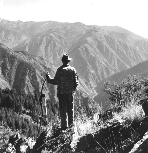 vintage man with bow and arrows looking over mountain valley canyon