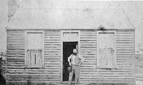 vintage man standing in doorway of cabin home