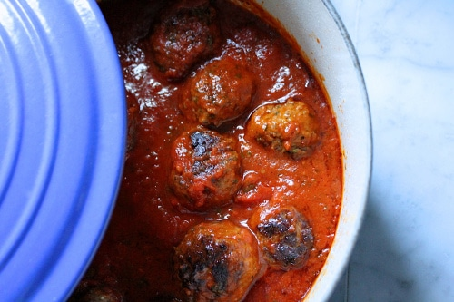 Cooked meatballs in red sauce ceramic le cruised dish.