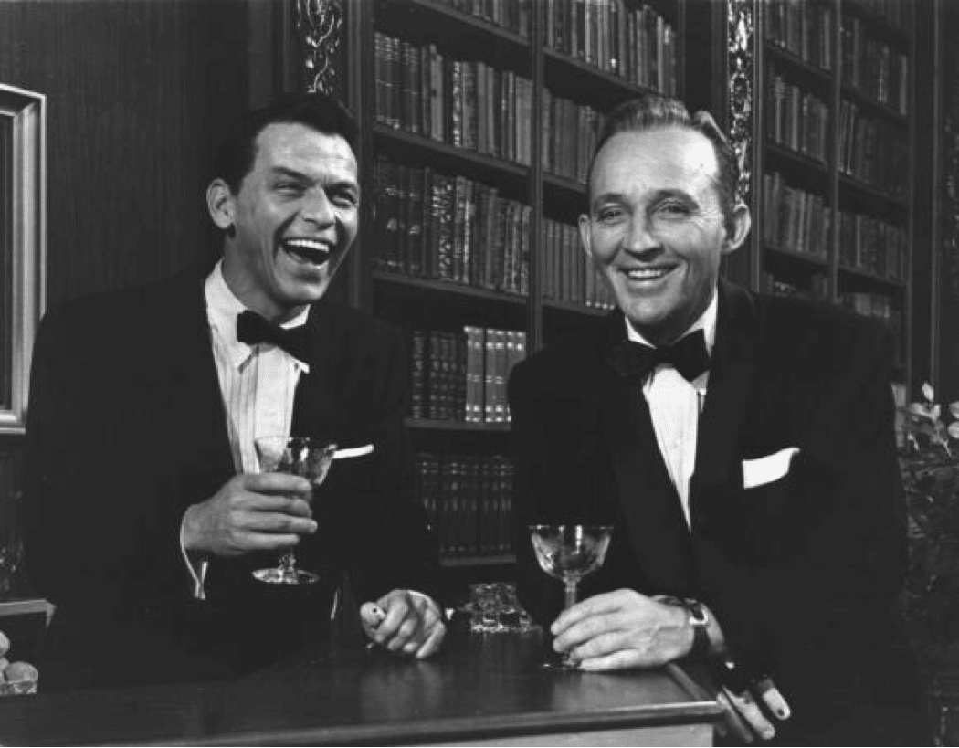 Sinatra drinking gin martini at a bard tuxedo laughing.