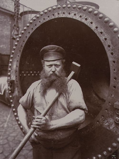 A long beard vintage blue collar worker with large sledgehammer.