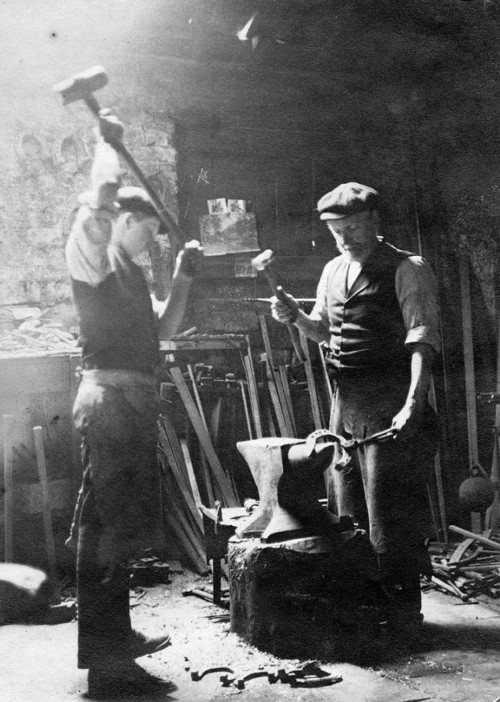 Vintage blacksmiths in workshop pounding anvil sledgehammer.