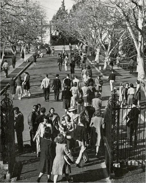 Vintage college campus students walking in and out of front gate.