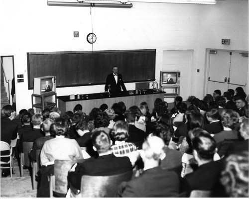 Vintage college class professor lecturing at front of classroom.