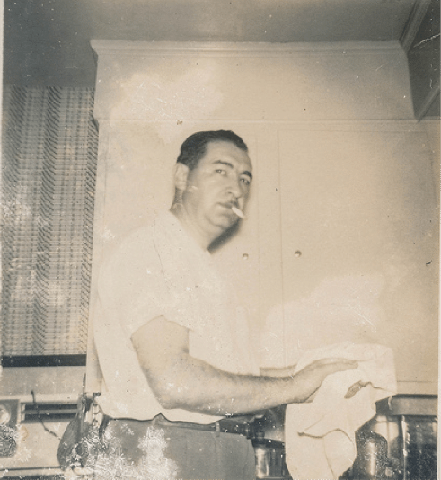 Vintage man it kitchen drying dishes smoking cigarette.