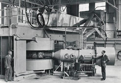 vintage men in laboratory warehouse working on large machine