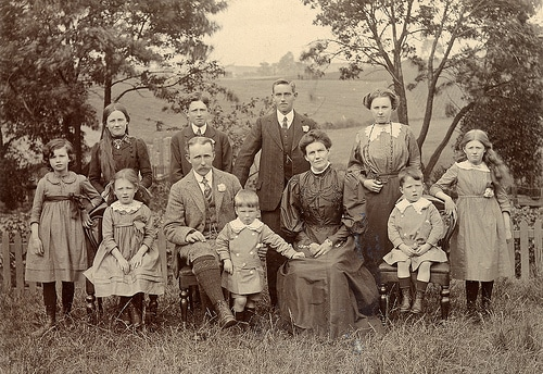 vintage family with a lot of kids sitting for portrait