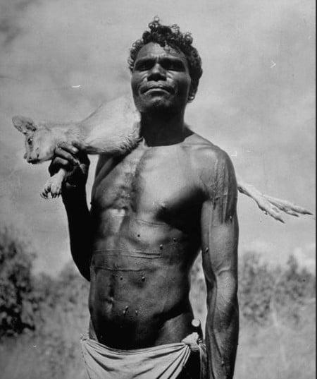 vintage african man hunter with dead animal over shoulder