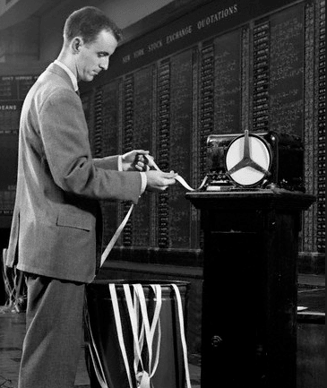 vintage man looking at stock tape coming out of machine