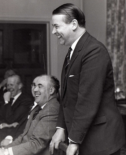 Vintage man standing at meeting smiling laughing.