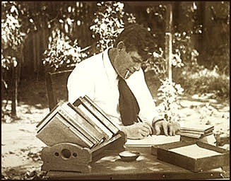 Jack london outside in yard writing on paper at desk by hand.