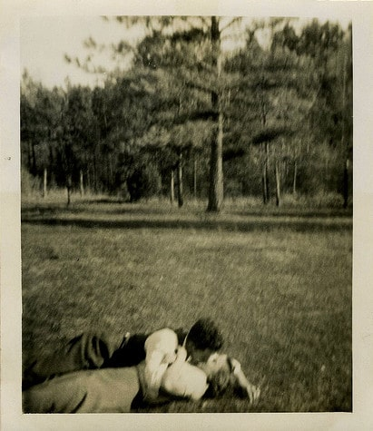 vintage couple man woman kissing in outdoor field