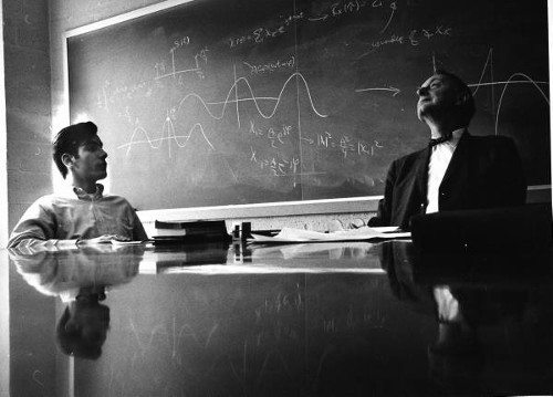 vintage college student talking with professor in classroom