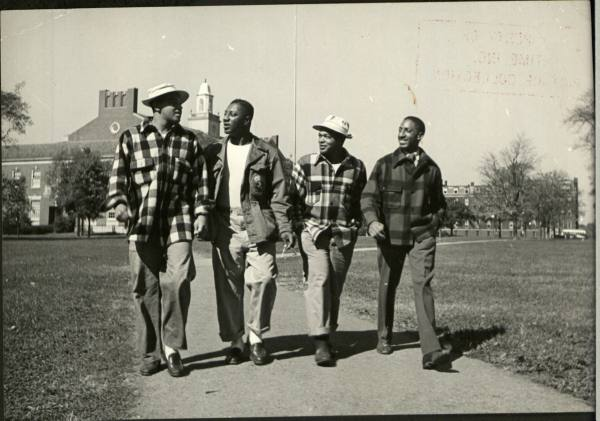 Four Vintage college African & American black friends talking each other on campus.