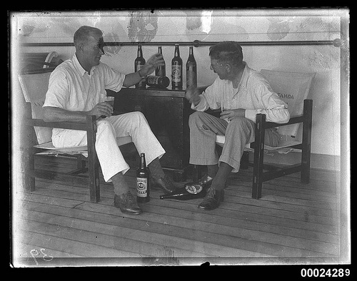 Vintage men sitting in chairs talking with beer bottles.