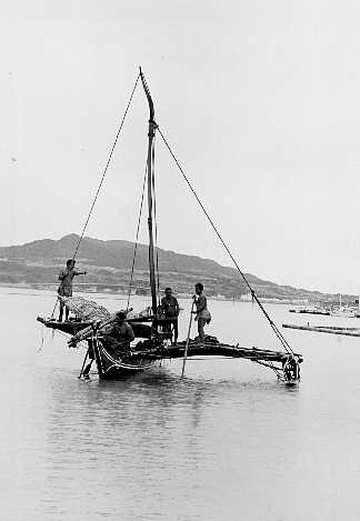trukese native indian men on sailboat in water