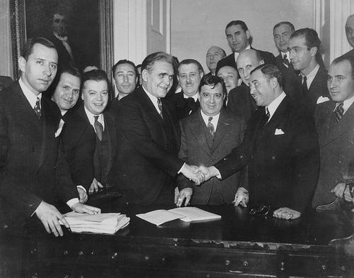 Vintage men suits shaking hands big group around behind them.