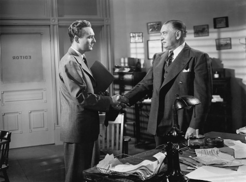 vintage businessmen in suits shaking hands in office