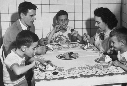 vintage family eating dessert at dinner table