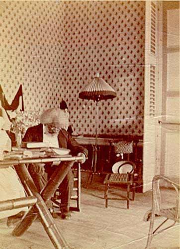 Frederick Douglass reading books in room.