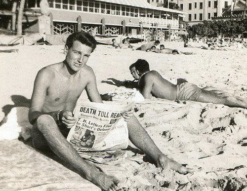 Vintage man reading newspaper at beach.