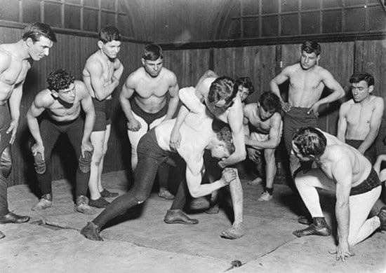 vintage men wrestling boxing in small gym with other men looking on