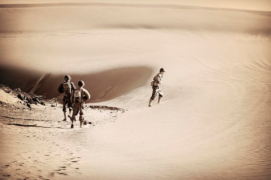 vintage military soldiers walking rucking hiking in desert sand