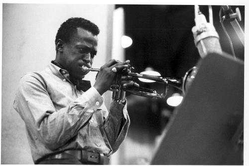 Miles Davis playing trumpet in studio.