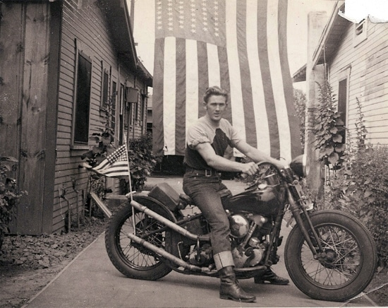 Vintage man sitting on motorcycle in front of american flag.