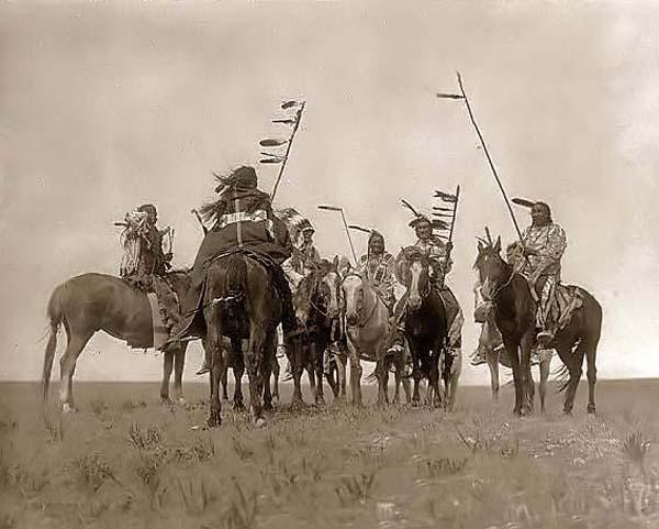 Vintage men riding on horses with flag poles.