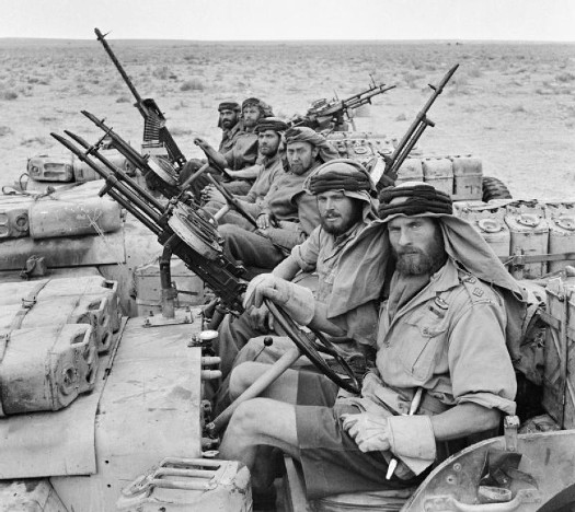 Vintage military soldiers with guns in desert trucks.