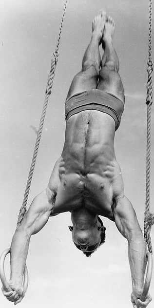 Vintage gymnast athlete hanging on gymnastic rings with both hands.