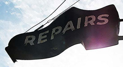 shoe repair sign shaped like a shoe