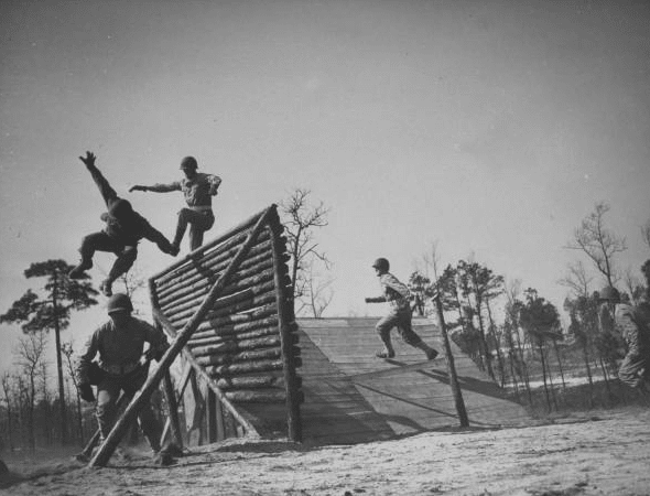 Vintage soldiers jumping over obstacle at bootcamp.