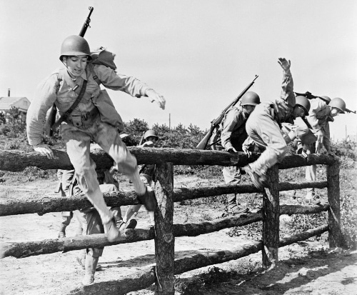 vintage soldiers at bootcamp jumping over wooden fence