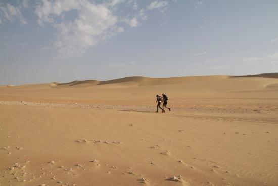 desert ultra marathon two men running side by side on sand