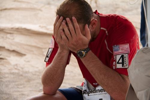 runner with hands in face exhausted desert ultramarathon