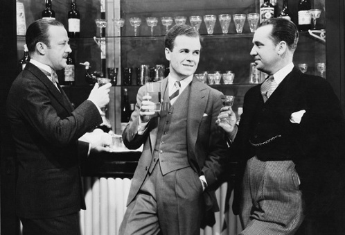 Vintage men drinking cocktails at bar.