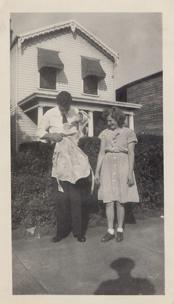 vintage man holding apron on sidewalk as woman looks on