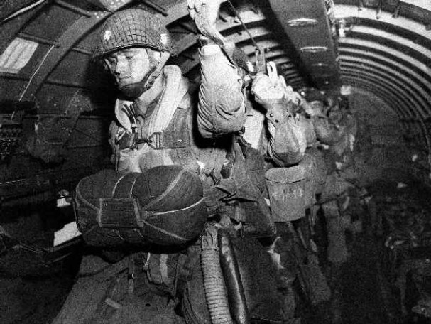 Vintage paratroopers getting ready to jump from airplane.