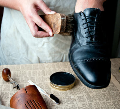 man brushing polishing black dress shoe close up photo