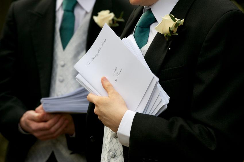 Wedding Ushers holding order booklets.