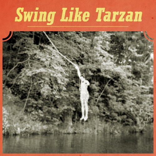 vintage young man swinging on rope swing into river