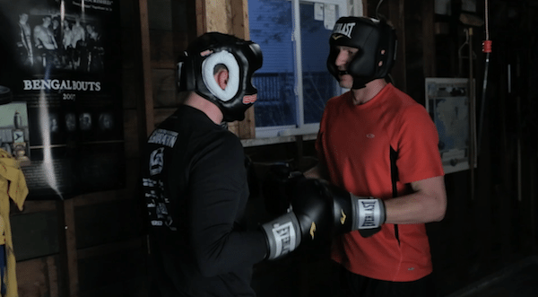Two men fighting sparring in garage home fight club.